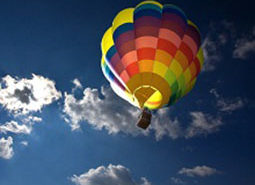 Hot air balloon in the blue sky and clouds